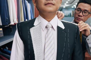 Tailor taking measurements