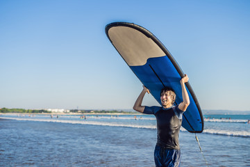 Man carrying surfboard over his head. Close up of handsome guy with surfboard on head at beach. Portrait of man carrying surfboard on hid head and smiling at beach