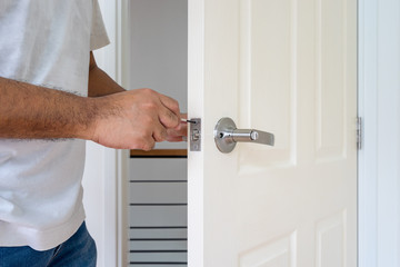 locksmith in white shirt fix white wood door