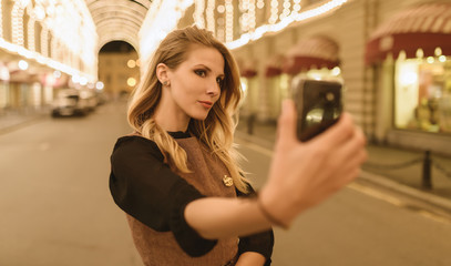 Young happy woman taking selfie at night. Selective focus. Color toned.