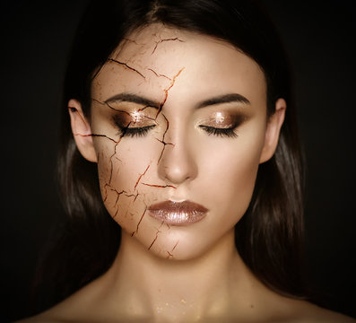 Woman with cracked face as cosmetic and dehydration effect concept.