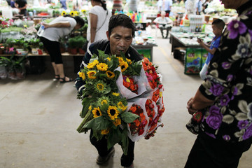 Vendor holding bouquets seeks customers at a flower market in Kunming
