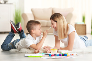 Mother with cute boy painting, indoors