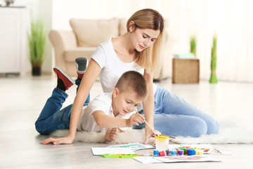 Mother with cute boy painting picture on sheet of paper, indoors