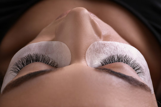 Young woman undergoing eyelash extensions procedure, closeup