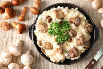 Composition with risotto and mushrooms on table, top view