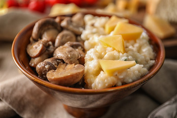 Bowl with risotto and mushrooms on table, closeup