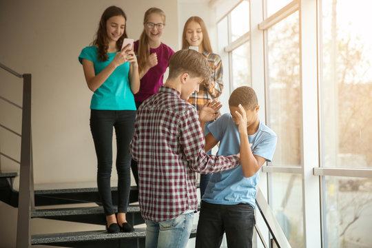 Teenager bullying African American boy indoors