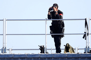 A policeman uses binoculars to survey the Place de la Concorde prior to the start of the traditional Bastille Day military parade which takes place under tight security on the Champs-Elysees Avenue in Paris
