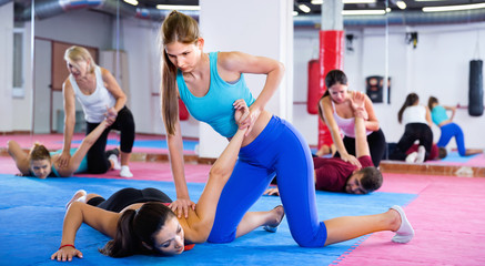 Women are doing self-defence moves in pairs in sporty gym.
