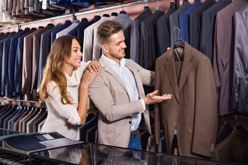 Couple deciding on new suit in men's cloths store