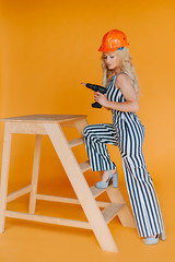 dangerous blonde.Attractive woman with a drill in her hands