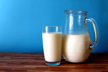 on the table is a jug and a glass of milk