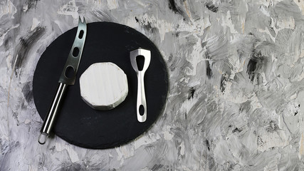 Round white cheese camembert or brie on a round shale board tasting with knives for cheese - Milk production. copy text. Flat top view, from above
