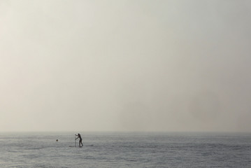 A woman paddles on a stand-up board during early morning fog in the sea near Kiti village