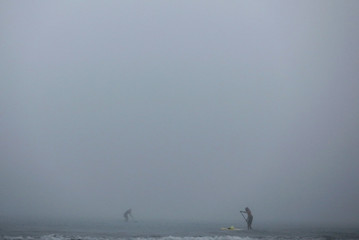 People paddle on stand-up boards during early morning fog in the sea near Kiti village