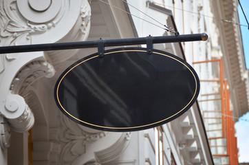 Oval shape signage in old city center. Blank surface for logo design mockup