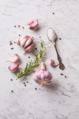 Garlic Cloves and Bulbs on white marble board.