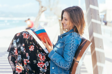 Happy woman relaxing at the seaside with a book
