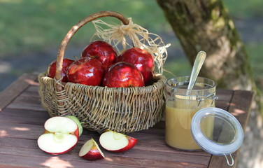 Korb mit roten Äpfeln, Apfelstücken und Apfelmus