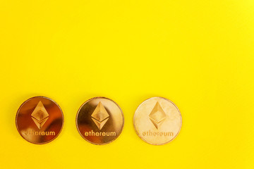 Crypto currency Ethereum, ETH, Crypto Coin. Macro shot of Ethereum golden coins isolated on yellow colourful trendy background. Blockchain technology, mining concept