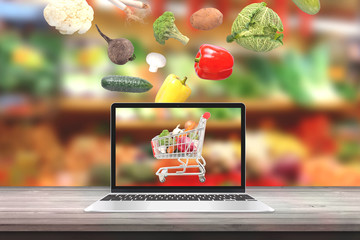 Buy fresh organic vegetables with laptop computer concept. Vegetables fall i cart on computer display.