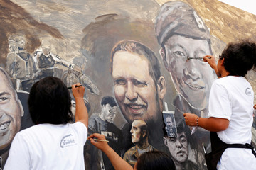 The portrait of Samarn Kunan, a former Thai navy SEAL who died during a recuse mission to save 12 soccer boys and their coach at Tham Luang cave complex, is painted on a giant painting in Chiang Rai