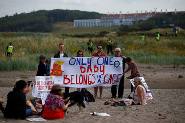 Demonstrators sit on the beach near the golf resort owned by U.S. President Donald Trump, during Trump's stay at the resort, in Turnberry