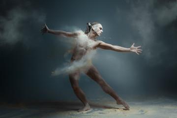 Dancing in flour concept. Long hair muscle fitness guy man male dancer in dust / fog. Guy wearing...