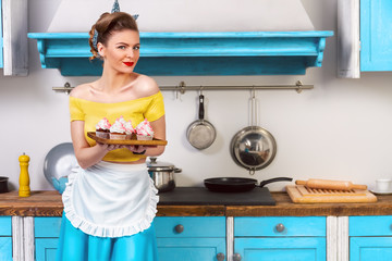 Retro pin up girl woman female housewife wearing colorful top, skirt and white apron holding tray with cooked sweet cupcakes standing in the kitchen with blue cabinets and utensils.