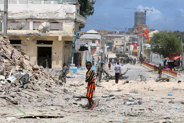 A boy stands near the scene where a speeding car exploded after it was shot at by police outside the hotels near the presidential palace, in Mogadishu