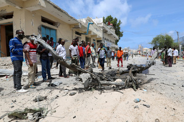 Civilians look at the wreckage of a vehicle destroyed at the scene where a speeding car exploded after it was shot at by police, outside the hotels near the presidential palace, in Mogadishu