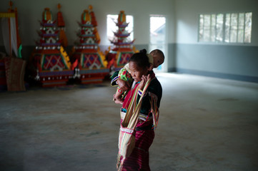 Dara-ang grandmother holding up her grandson at Prachao Tum Jai village, in the northern province of Chiang Rai