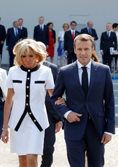French President Emmanuel Macron and his wife Brigitte Macron leave after the traditional Bastille Day military parade on the Champs-Elysees avenue in Paris
