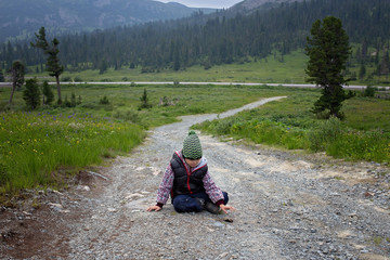 Tired and sad child sitting on a mountain path. To give up in overcoming difficulties. Rest of the child in the campaign