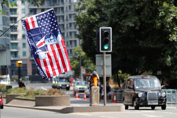 A Trump supporter holds a flag near the U.S. Embassy, ahead of a rally during the visit of U.S. President Donald Trump to Britain, in London