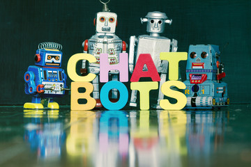 the word  CHAT BOTS with rtro robots on a wooden floor 1