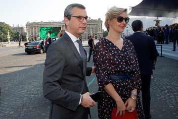 French general secretary of the presidency Alexis Kohler and his wife Sylvie Schirm arrive to attend the traditional Bastille Day military parade on the Champs-Elysees in Paris