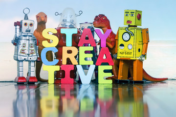 the word STAY CREATIVE with wooden letter dinosaurs