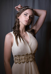 Summer portrait of young beautiful lady wearing long white evening dress posing in the studio.