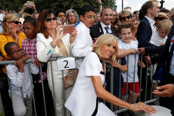 Brigitte Macron, wife of French President Emmanuel Macron, poses for pictures with people after the traditional Bastille Day military parade on the Champs-Elysees in Paris