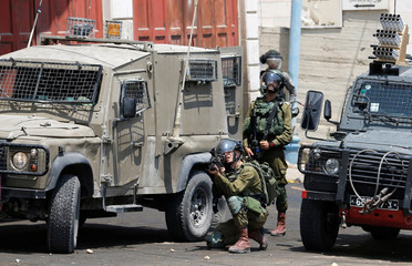 Israeli soldiers take position during clashes with Palestinian protesters near Hebron in the occupied West Bank