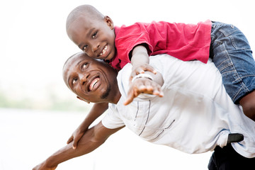 young father carrying his son smiling on his back