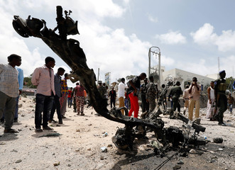 Somali security officers and civilians look at the wreckage of a vehicle destroyed at the scene where a speeding car exploded after it was shot at by police, outside the hotels near the presidential palace, in Mogadishu