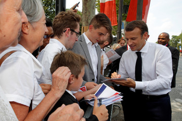 French President Emmanuel Macron signs autographs after the traditional Bastille Day military parade on the Champs-Elysees avenue in Paris