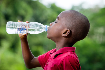 little boy drinking mineral water outdoors