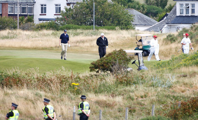 U.S. President Donald Trump walks at his golf resort under the gaze of police officers, in Turnberry