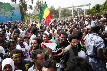 People celebrate during the welcoming ceremony of Eritrea's President Isaias Afwerki arriving for a three-day visit, at the Bole international airport in Addis Ababa