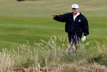 U.S. President Donald Trump gestures as he walks on the course of his golf resort, in Turnberry