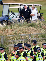 U.S. President Donald Trump looks towards police officers on the course of his golf resort, in Turnberry